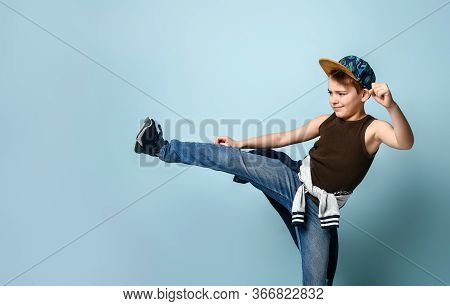 Brutal Teen Boy In Jeans, Sleveless Shirt And Cap Doing Side-kick And Swinging A Punch Ready To Figh