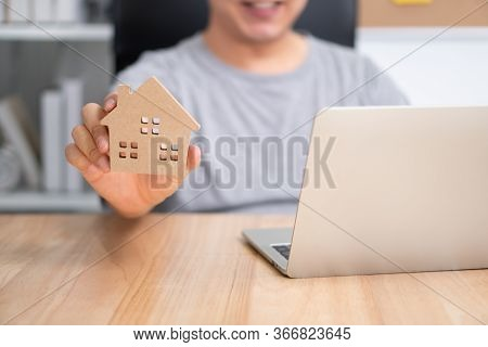 Smiling Businessman Holding A Wooden House In Home Workspace. The Concept Of Working From Home Until