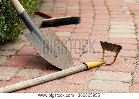 Old Rusty Garden Tools Laying On Stone Paved Walkway With Gray And Pink Pavements. Used Hoe, Shovel