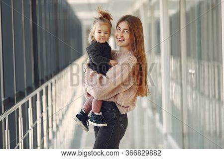 Mother With Little Daughter Standing In A Hall