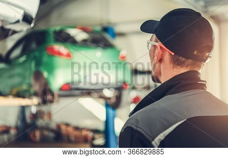 Auto Mechanic Walking Towards Car Lift With Vehicle Suspended In Air In Repair Shop.