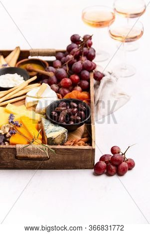 Tray With Cheese Assortment Served With Rose Wine For A Light Summer Snack, Front View, Blank Space