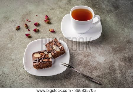 Homemade Brownie With Almonds On A Saucer With A Fork On Wooden Table. Next Cup Of Tea And Rose Buds