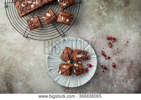 Homemade Brownies With Almond Petals And Rosebuds On A Textured Plate On A Wooden Background. Top Vi