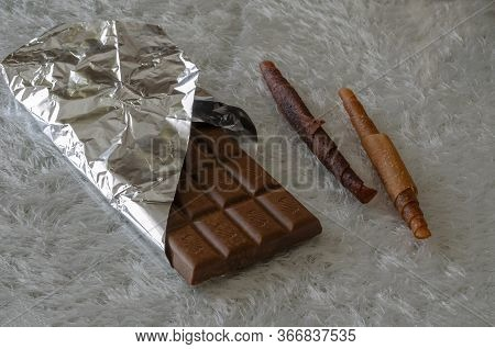 A Bar Of Open Chocolate And Two Pieces Of Fruit Candy On A White Fleecy Background. Chocolate In Foi