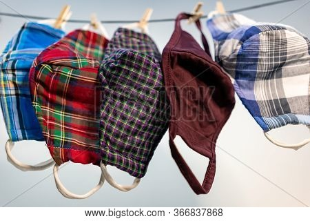 Different Colors Of Washable Face Masks Hanging To Dry After Washing. Fashionable Face Masks Reusabl