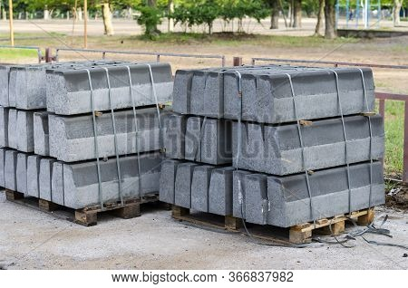 New Road Curbs On The Pallet. Large Gray Curbs On Wooden Pallets. Tied With Plastic Bondage Tape. Ma