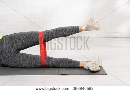 Cropped View Of Sportive Woman Exercising With Resistance Band On Fitness Mat