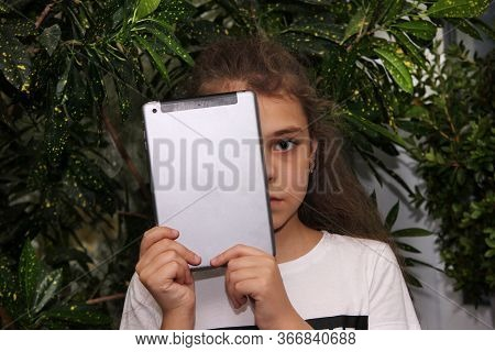 The Girl Holds A Digital Tablet In Front Of Her Face, Covering Half Of Her Face. One Eye. To Spoil Y