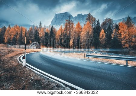 Blurred Car On Winding Road In Mountains In Overcast Rainy Evening In Autumn. Dramatic Landscape Wit