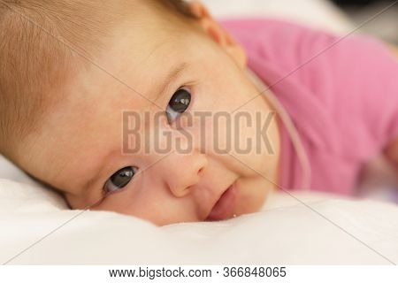 Little Newborn Lying On Her Stomach On A White Bed. The Newborn Is Awake Looking Around In The Room.