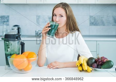 Woman Drinking Green Spirulina In A White Kitchen. Detox. Perfect Body And Calorie. Vegan Meal Diet