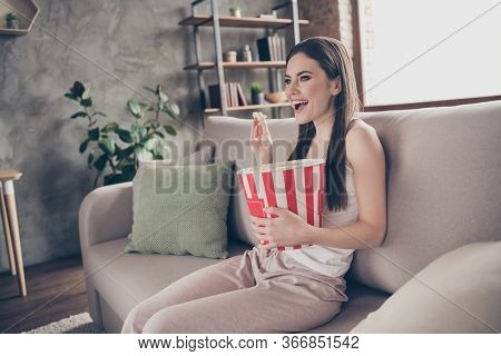 Profile Side Photo Of Cheerful Candid Girl Sit Divan Hold Big Box Eat Pop Corn Watch Interesting Fil