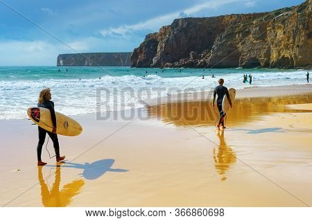 Sagres, Portugal - October 30, 2018: Young Men Walking By Sandy Beach With Surfboard. Algarve Is A F
