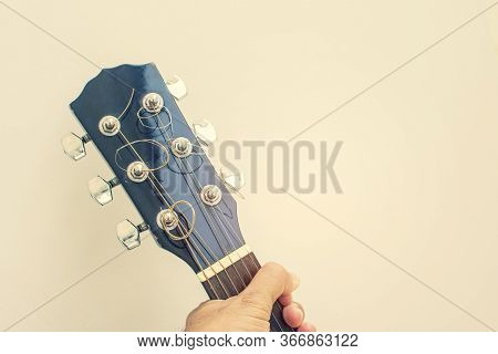 Hand Holding Headstock Of Guitar With A Copy Space.