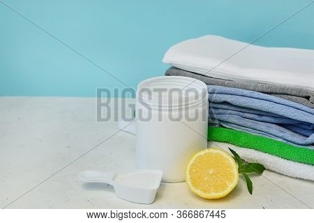 Washing Powdwashing Powder And A Stack Of Clean Clothes On A White Background. Copy Space. Cleanline