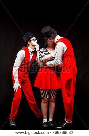 Portrait Of Three Mime Artists, Isolated On Black Background. A Man Watches A Woman And A Man Kissin