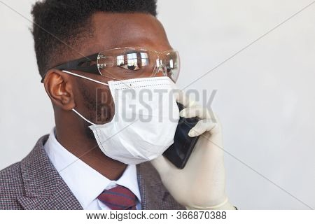 Covid-19. Handsome African Black Man In A Suit Is Using Medical Mask, Protective Glasses And Holding