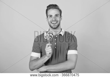 Sweet Boy. Symbol Of Happiness. Man Eat Lollipop. Man Smiling Hold Lollipop. Holiday Concept. Sugar
