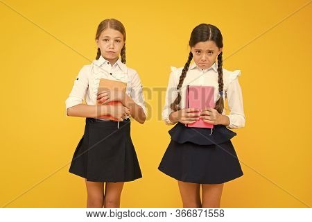 Unhappy Bookworms. Unhappy Little Schoolchildren On Yellow Background. Adorable Small Girls With Unh