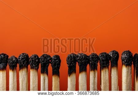Row Of Burnt Matches. Many Burnt  Matches On Orange Background, Closeup. Copy Space.