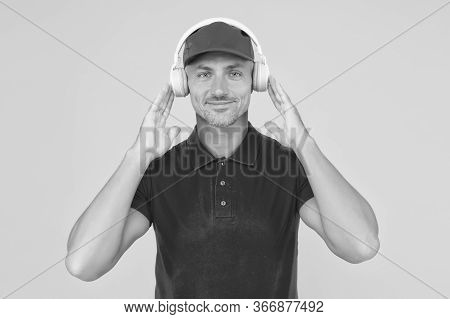Best Sounding Headphones. Happy Guy Wear Headphones Yellow Background. Handsome Man Listen To Music
