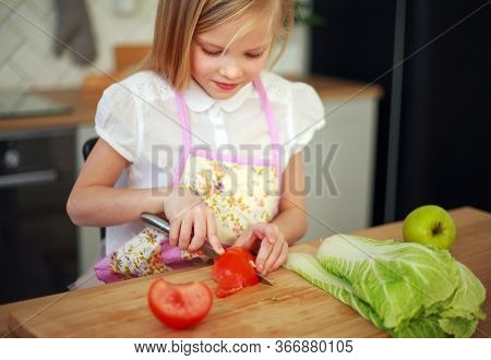 Little Girl Child Cuts Tomatoes Cooks Salad At A Table In The Kitchen, Healthy Food