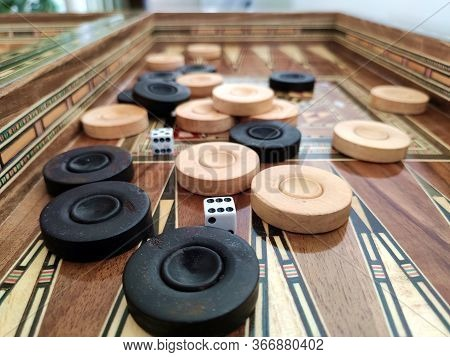 Backgammon With Wooden Inlay. Wooden Backgammon Board Game Of Pearl Inlaid On Brown Background.