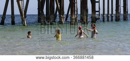 Adelaide, Australia - March 8th, 2020:a Group Of Children Playing In The Shallow Water Near A Wharf