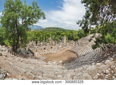 Phaselis, Turkey - May 19, 2018. Tourists Walk Into Ruins Of Amphitheatre Of Ancient Phaselis City.