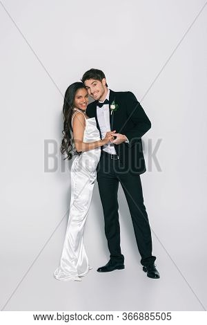 Full Length View Of Happy, Elegant Interracial Newlyweds Holding Hands And Smiling At Camera On Whit