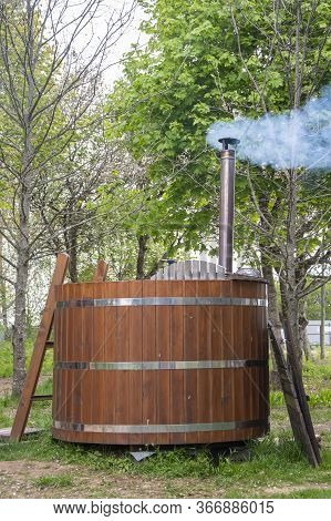 A Wooden Outdoor Bath Font Stands On The Grass In The Courtyard. Concept: Sauna And Steam Room, Outd