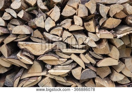 Chopped Wood For Lighting A Fire Is Stacked In A Woodpile, Backgrounds And Texture.