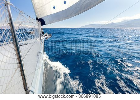 Sailing with fresh speed wind. A view from the yacht's deck to the bow and sails. Sail boat with set up sails gliding in open sea. Greece, Europe