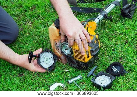 Worker Repairs Starter In Trimmer Or Lawn Mower That Lies On The Grass