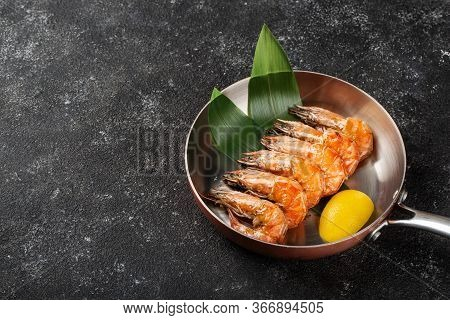Grilled Tiger Prawns Are Served In A Pan With A Slice Of Lemon. Free Space For Text On A Dark Backgr