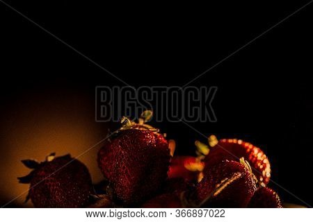 Red Juicy Ripe Strawberries On A Black Background. Sun Warm Rays, Back Light