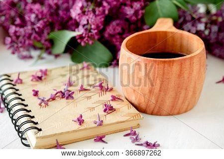 Wooden Finnish Cup With Coffee On The Table. Nearby Lies A Closed Notebook For Notes And A Bouquet O
