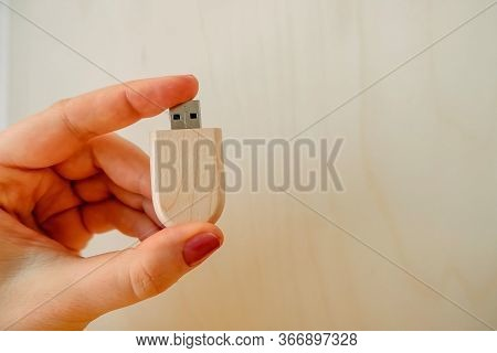 Female Hand Holds A Stylish Wooden Flash Drive On A Light Background. Beautiful Photo Feedback To Th
