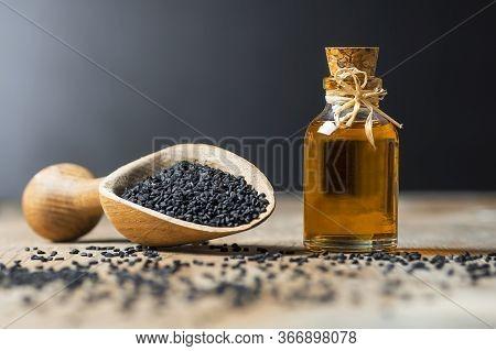Glass Bottle Of Black Cumin Seeds Essential Oil , Nigella Sativa In Spoon On Wooden Background. Orga