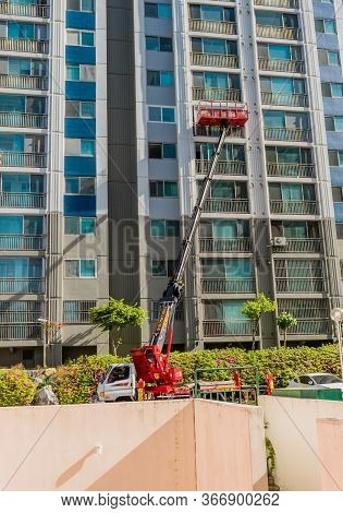Daejeon, South Korea; May 13, 2020: Lift Truck With Arm Extended Moving Furniture Out Of Highrise Ap