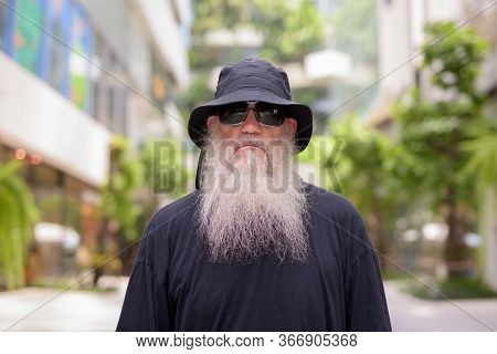 Mature Bearded Hipster Man Wearing Hat And Sunglasses For Protection From The Sun And Hot Weather In