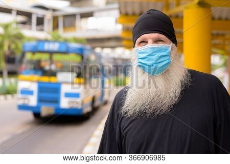 Mature Bearded Hipster Man Wearing Mask For Protection From Corona Virus Outbreak And Pollution At T