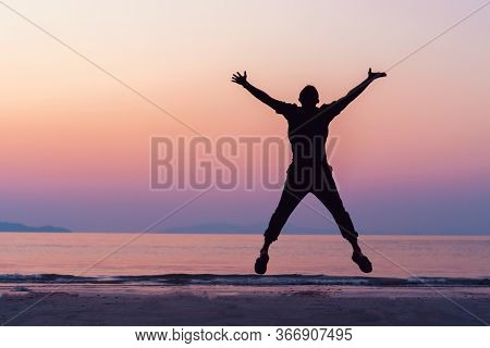 Silhouette Man Rise Hands Up And Jump To Sky Freedom Concept With Sunset Sky And Summer Beach Season