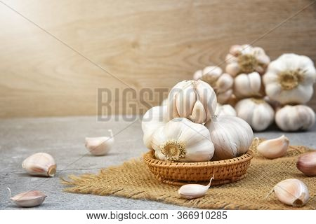 Organic Garlic. Fresh Garlic Cloves And Garlic Bulb In Wooden Basket On Dark Background With Pile Of