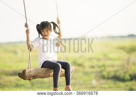 Little Girl Is Swinging At Play Ground