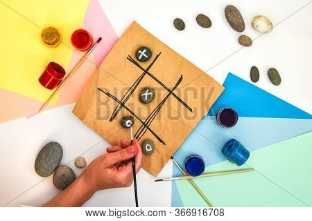 Top View Of Tic Tac Toe Game With Stones Marked With Naughts And Crosses. Childrens Art Project, A C