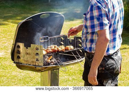 A Man At The Charcoal Grill Uses Grill Tongs To Place The Already Seasoned Raw Meat On The Grill. Se
