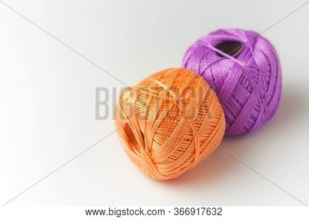 Two Skeins Of Thread In Purple And Orange. Knitting Threads On A White Background. Hobby.