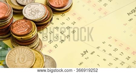 Stack Of Coins On Calendar, Closeup Shot, For Finance Background